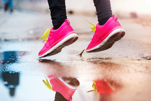 Unrecognizable young woman running in rainy weather