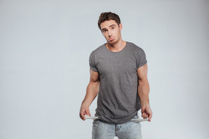 Upset casual man showing his empty pockets over white background