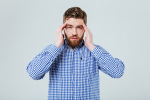Upset depressed young man touching his temples and having headache over white background
