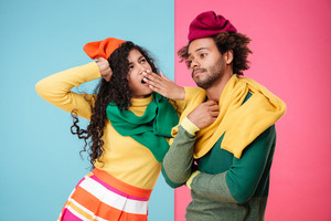 Upset exhausted african american young couple in hats and scarves standing and yawning