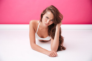 Upset pretty woman in white swimsuit lying and looking at camera isolated on the pink background