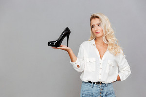 Upset sad woman holding shoes on her palm over gray background