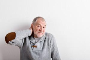 Upset senior man in gray sweater, having ache in his neck. Studio shot against white wall.