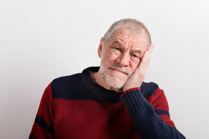 Upset senior man in red and blue sweater holding head. Studio shot against white wall.