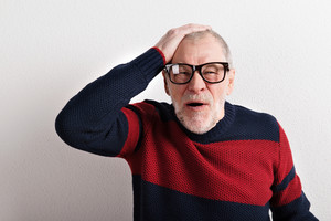 Upset senior man with headache holding head, wearing red and blue sweater and black eyeglasses. Studio shot against white wall.