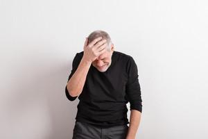 Upset senior man with headache holding his head, wearing black t-shirt. Studio shot against white wall.
