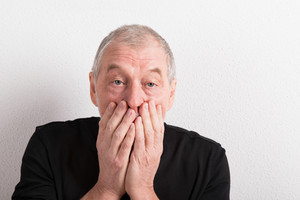 Upset senior man with headache holding his mouth, wearing black t-shirt. Studio shot against white wall.