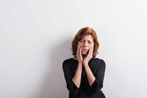 Upset senior woman in black t-shirt, holding head, having headache or toothache. Studio shot against white wall.
