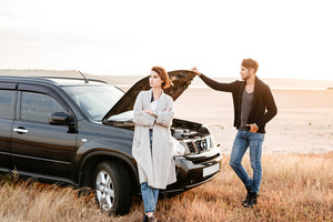 Upset young couple standing near car with open hood outdoors