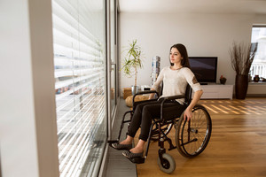 Upset young disabled woman in wheelchair at home in her living room, looking out the window