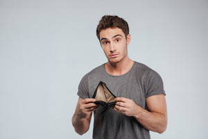 Upset young man holding empty wallet over white background