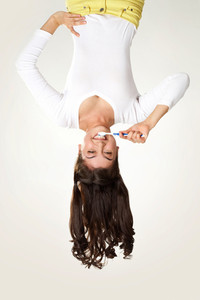 Upside down view of happy girl brushing teeth on white background