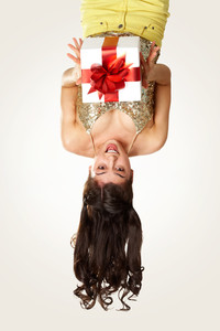 Upside down view of young girl with giftbox on white background