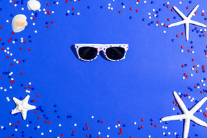 USA holiday decorations with sunglasses on a blue background flat lay