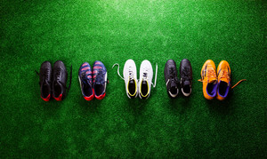 Various colorful cleats against artificial turf, studio shot on green background. Flat lay, copy space.