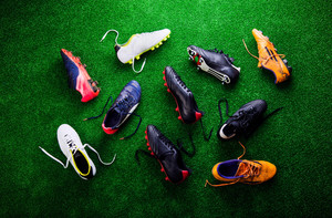 Various colorful cleats against artificial turf, studio shot on green background. Flat lay.