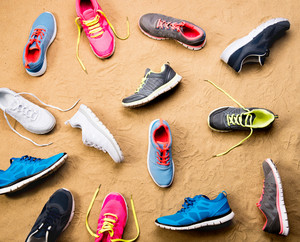Various colorful sports shoes laid on sand beach background, studio shot, flat lay.