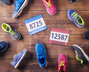 Various running shoes and race numbers laid on a wooden floor background