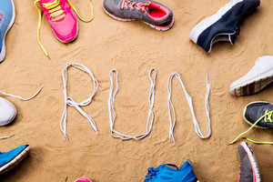 Various running shoes and run sign made of shoelaces against sand background, studio shot, flat lay