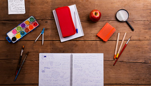 Various school and art supplies laid on desk, flat lay, notebook with math symbols and formulas. Studio shot on wooden background.