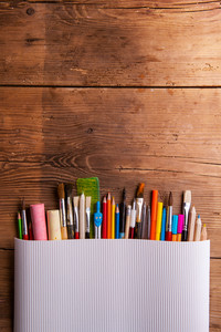 Various school and art supplies laid on table, flat lay. Studio shot on wooden background, copy space
