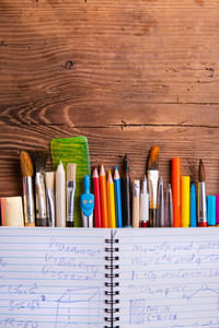 Various school and art supplies on table under notebook with mathematical symbols and formulas, flat lay, copy space