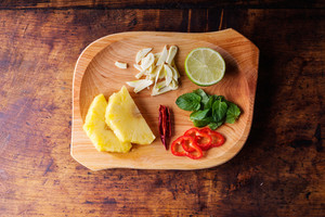 Various types of fruit and vegetables laid on a plate. Studio shot on wooden background.