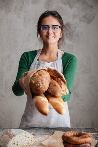 Vertical image of a happy female baker showing bag with bread and looking at the camera