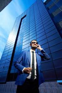 Vertical image of a smiling businessman speaking on the phone