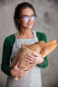 Vertical image of a smiling female baker holding bag with bread and looking away