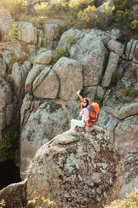 Vertical image of adventure woman on the rock. near the canyon
