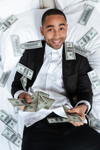 Vertical image of African man in suit lying on bed in hotel room and throws the money. Top view