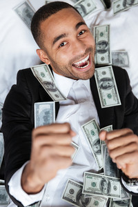 Vertical image of African man in suit lying with money on bed in hotel room. Top view. Close up