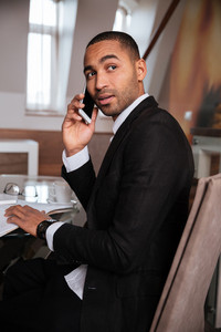 Vertical image of african man in suit sitting on chair, talking at phone and looking at camera