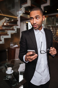 Vertical image of african man in suit with phone and glasses looking away in hotel