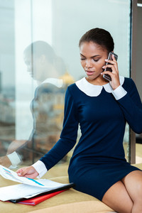 Vertical image of afro business woman in dress sitting near the window with documents and talking at phone