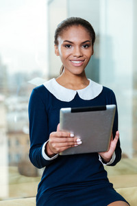 Vertical image of afro business woman in dress with tablet computer sitting near the window and looking at camera in office