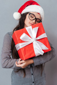 Vertical image of asian girl in christmas hat holding gift with eyes closed. Isolated gray background