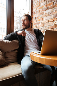 Vertical image of Bearded man sitting by the table and using laptop in cafe and looking away