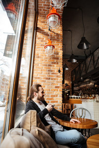 Vertical image of Bearded man sitting by the table near the window in cafe with cup of coffee. Side view