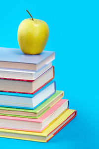 Vertical image of books with green apple
