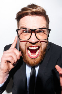 Vertical image of Business man in glasses and suit screaming in phone and looking at camera. Isolate gray background