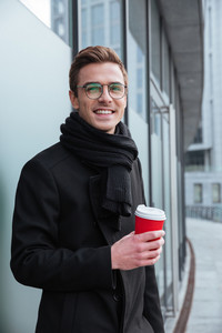 Vertical image of Business man in glasses and warm clothes standing sideways and drinking coffee outdoors.