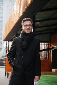 Vertical image of business man in glasses and warm clothes walking on the street with arm in pocket