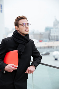 Vertical image of business man in glasses and warm clothes with folder outdoors
