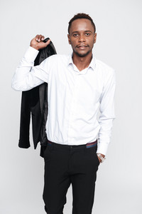 Vertical image of calm african man in shirt holding jacket on shoulder with arm in pocket and looking at camera. Isolated white background