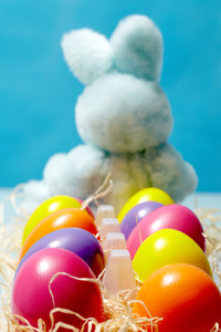 Vertical image of colorful painted Easter eggs with toy rabbit on background