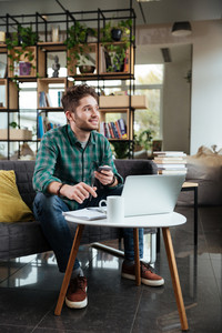 Vertical image of handsome man in green shirt sitting on sofa by the table with laptop and cup of tea and writing something in office. Full length. Coworking