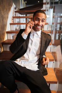 Vertical image of Happy African man in suit using phone lying on stairs. Front view