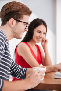 Vertical image of happy couple sitting by the table with laptop in office. Focus on man